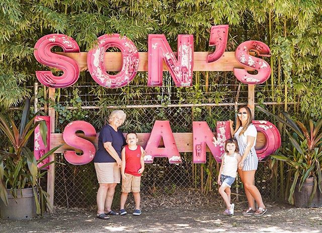 Family posing in front of Son's Sand sign.| Son's Island in Seguin, Texas