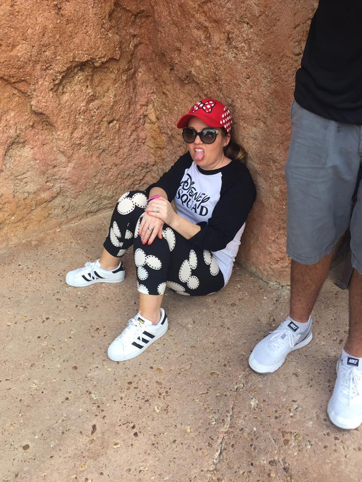 Woman dressed in Disney gear sitting down exhausted in Disney World.  Celebrating A Wedding Anniversary at Walt Disney World