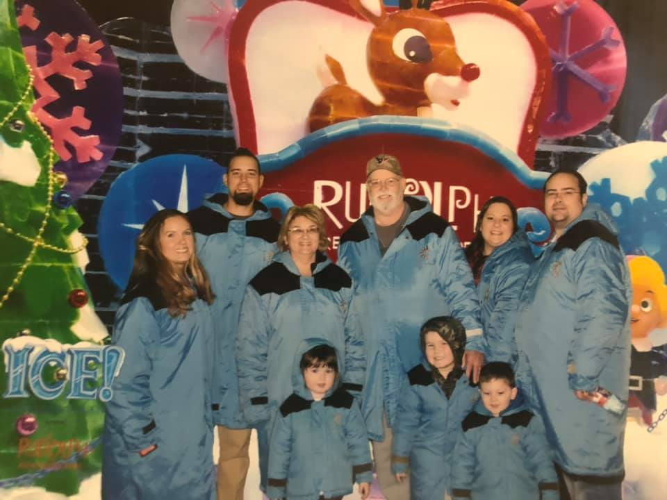 Group of people posing in front of Gaylord sign. | Christmas at the Gaylord Texan Hotel