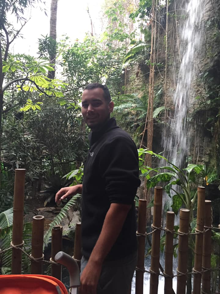 Man posing with waterfall at the Dallas World Aquarium in Dallas.| Weekend in Dallas with Kids