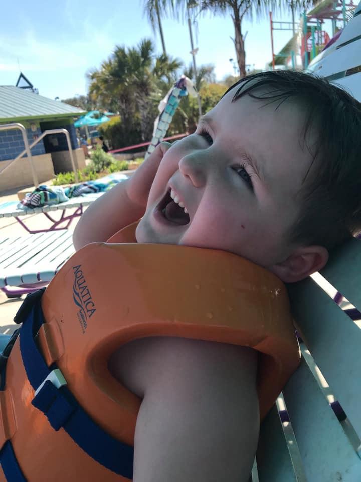 Little kid laughing on lounge chair at the pool at SeaWorld in San Antonio.   Week in San Antonio, Texas