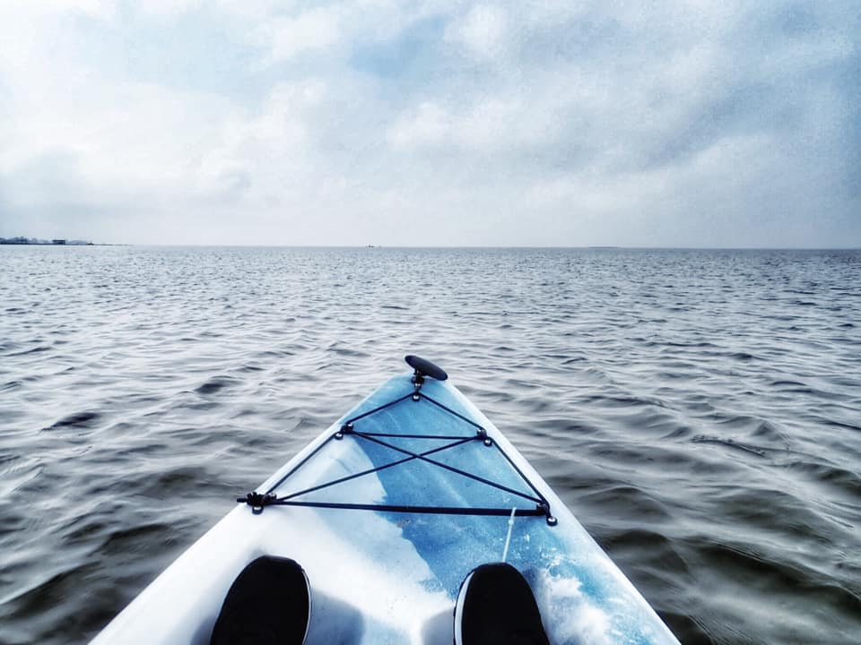 """The front of a kayak in the water in Galveston.   Adult Weekend in Galveston, Texas; on """"The Strand"""""""
