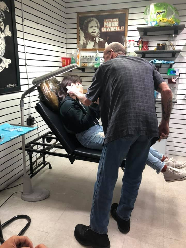 """Girl getting ear pierced in Galveston.   Adult Weekend in Galveston, Texas; on """"The Strand"""""""