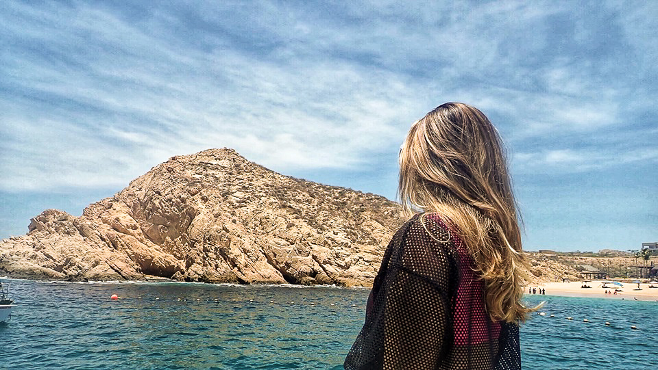 Woman enjoying the rocks and water on a boat ride in Cabo.   Cabo, Mexico- The Best All Inclusive Vacation