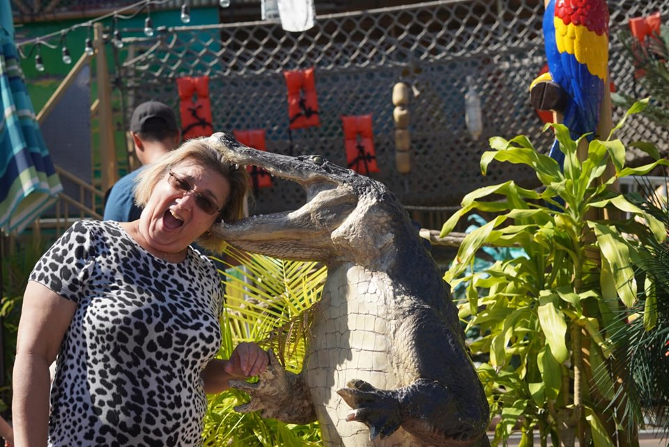 Woman posing with biting alligator statue at the fair. | State Fair of Texas-Dallas