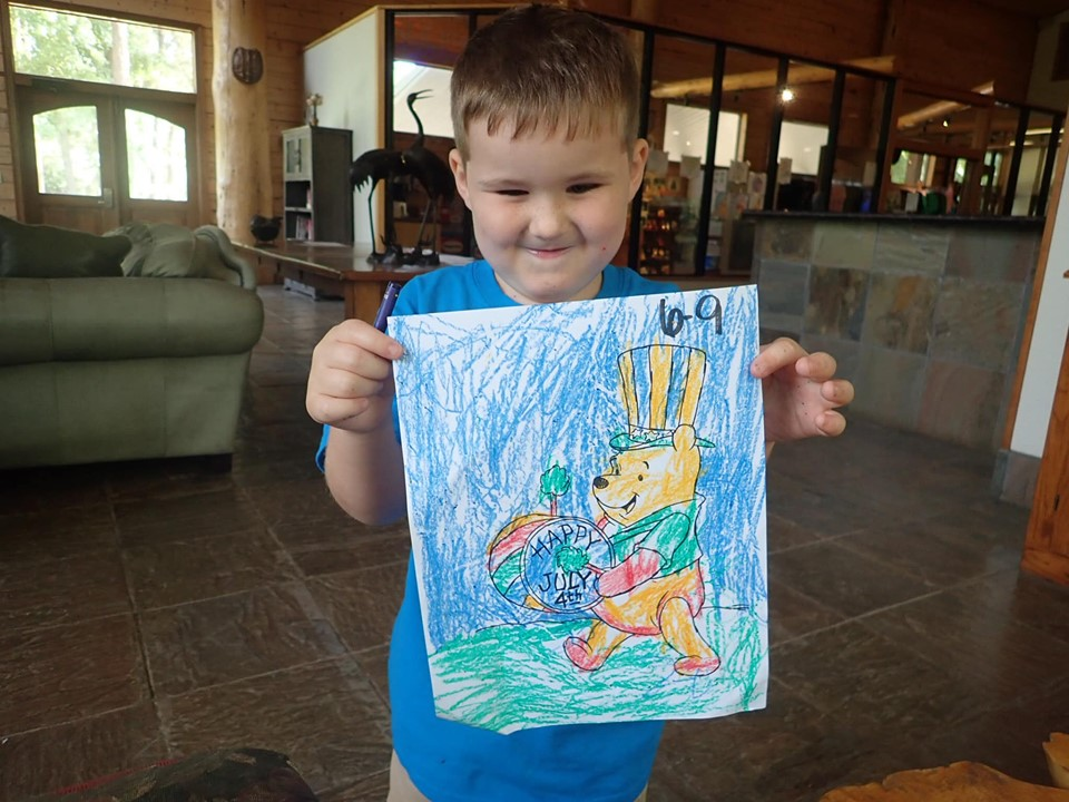 Little boy showing off his coloring page at the lake.| The Retreat at Artesian Lakes in Texas