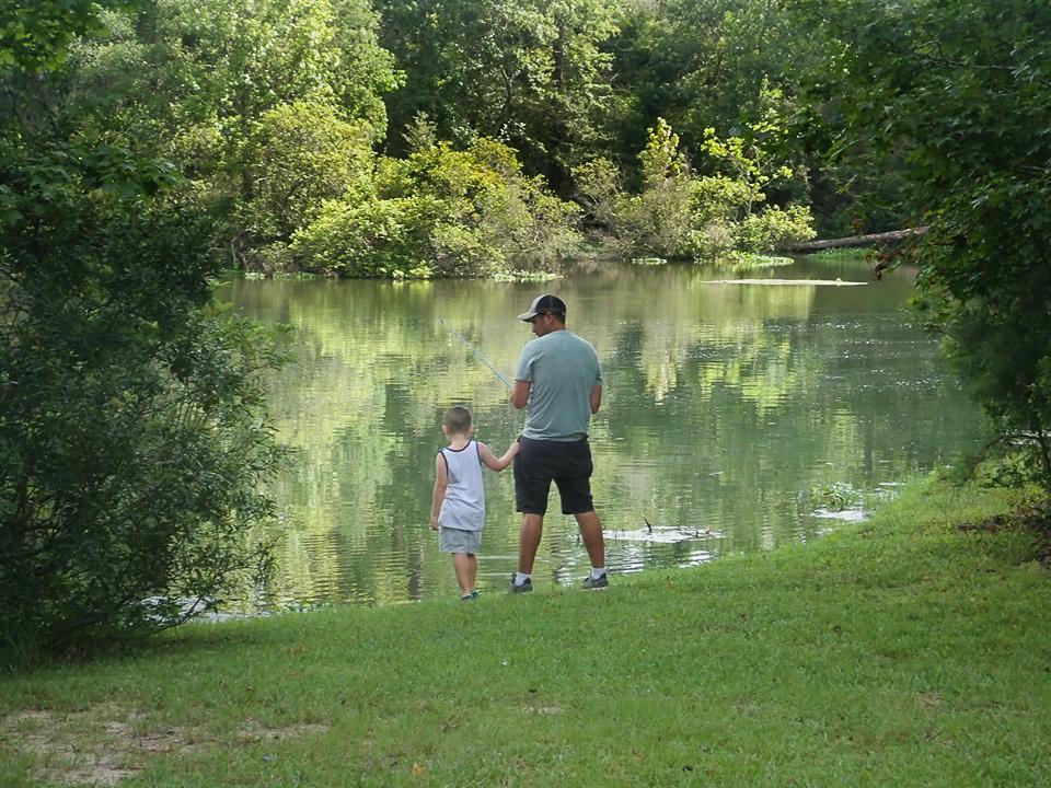 Man fishing with his son at the lake.| The Retreat at Artesian Lakes in Texas