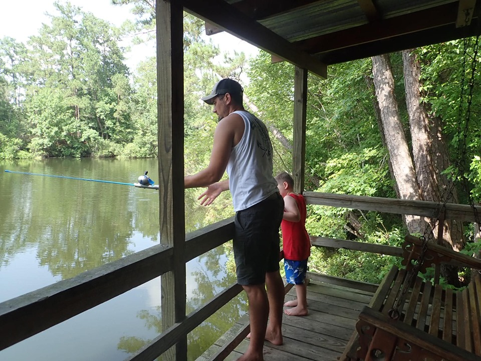 A man and a little boy fishing off the porch of the retreat cabin in the woods at the lake.| The Retreat at Artesian Lakes in Texas