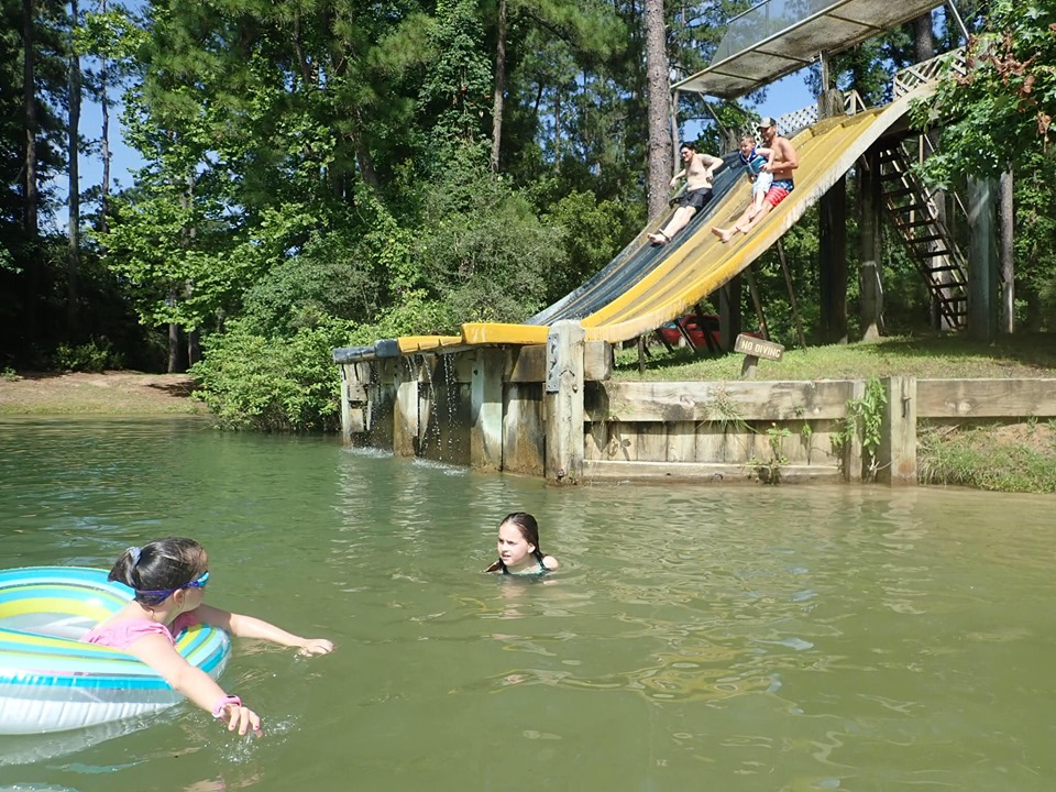 People riding water slides into the lake.| The Retreat at Artesian Lakes in Texas