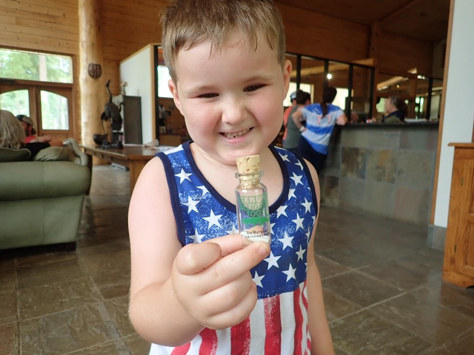 Little boy holding scavenger prize at the lake.| The Retreat at Artesian Lakes in Texas
