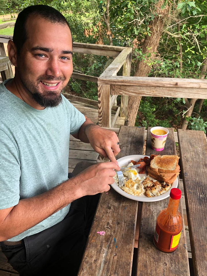 Man eating breakfast on the porch of the cabin at the lake.| The Retreat at Artesian Lakes in Texas