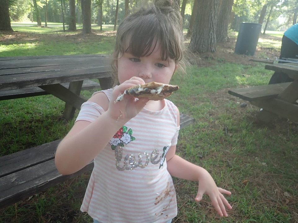 Little girl eating s'mores at the lake.| The Retreat at Artesian Lakes in Texas