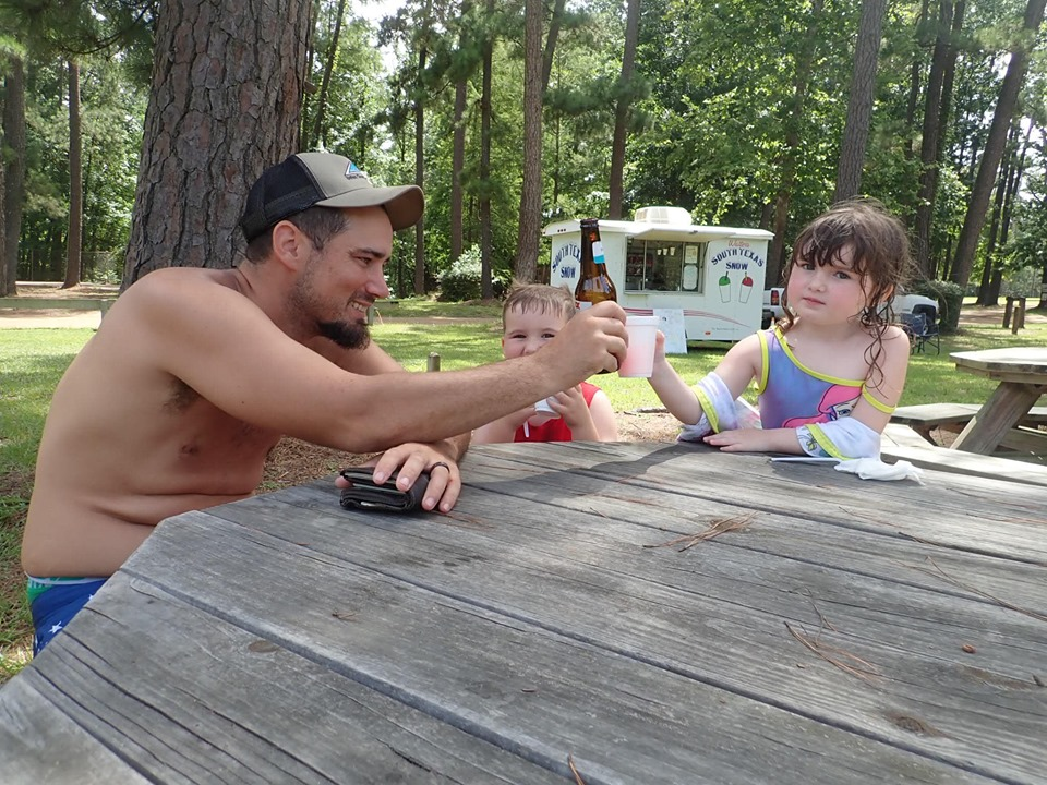 Man with two kids eating snow cones at a picnic table at the lake.| The Retreat at Artesian Lakes in Texas