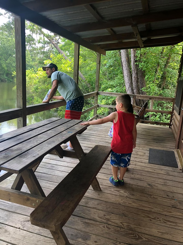 People on the porch of the retreat cabin in the woods at the lake.| The Retreat at Artesian Lakes in Texas