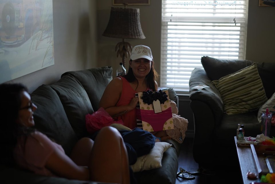 Woman opening gifts on the couch in the townhouse at Corpus Christi.   Corpus Christi Bachelorette Weekend