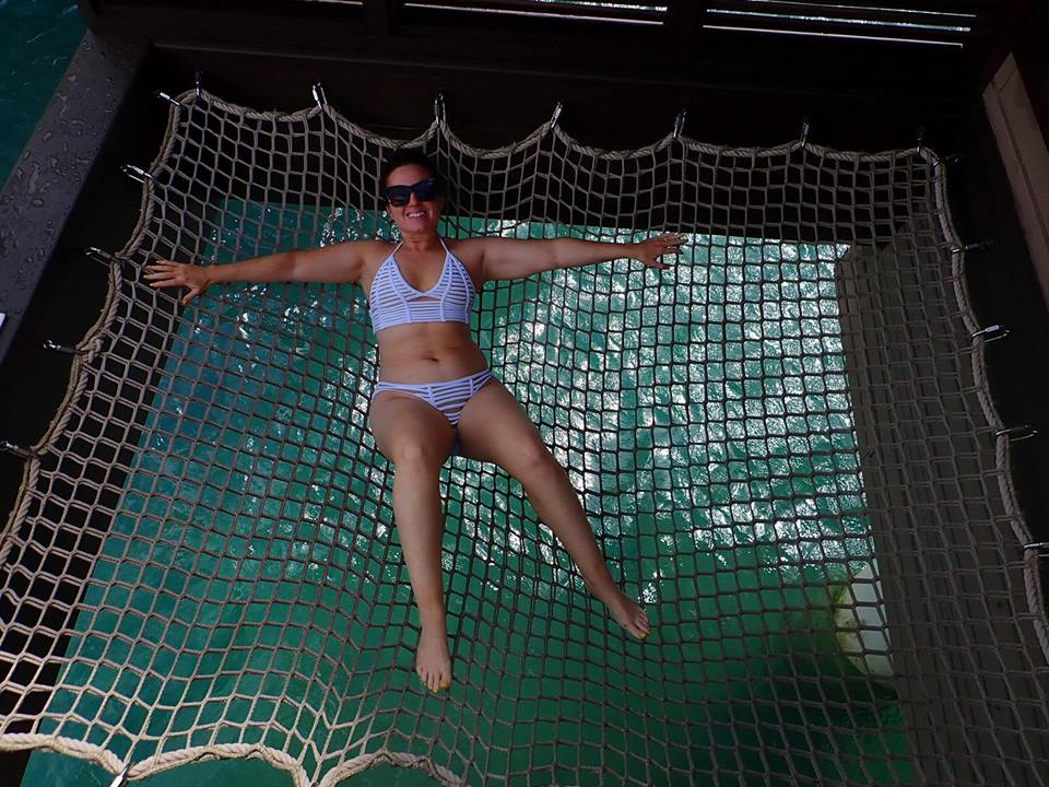 Woman laying on hammock at Sandals resort in Jamaica.   Jamaica Over-Water-Bungalows