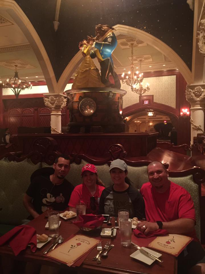 Two couples posing at table during dinner at Be Our Guest restaurant at Disney World.   Celebrating A Wedding Anniversary at Walt Disney World