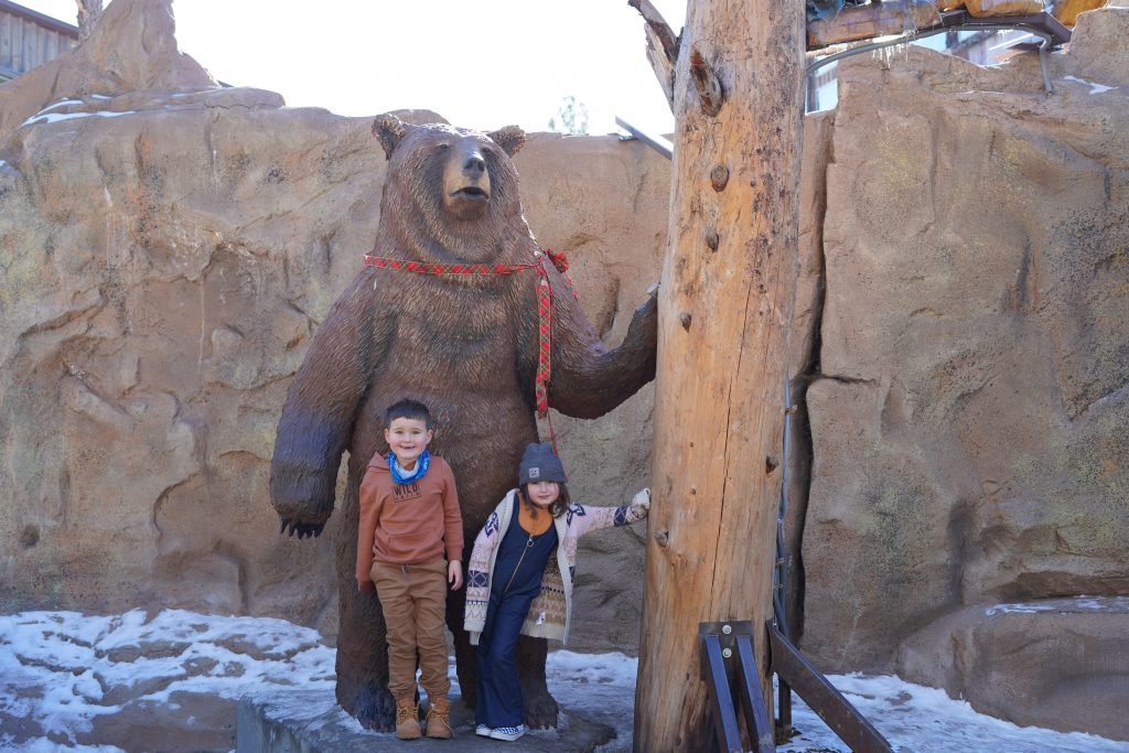 Two kids posing in front of a fake big brown bear in Bearizona. | Williams, Arizona on Route 66 with Kids