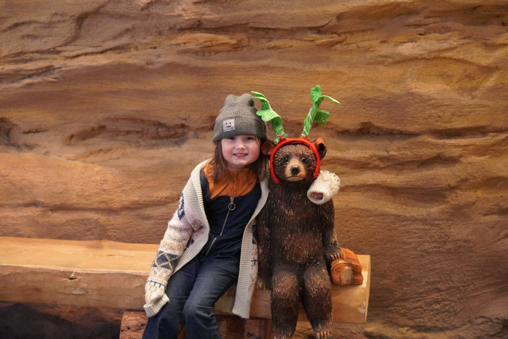 Little girl hugging fake baby bear on a bench at Bearizonia. | Williams, Arizona on Route 66 with Kids