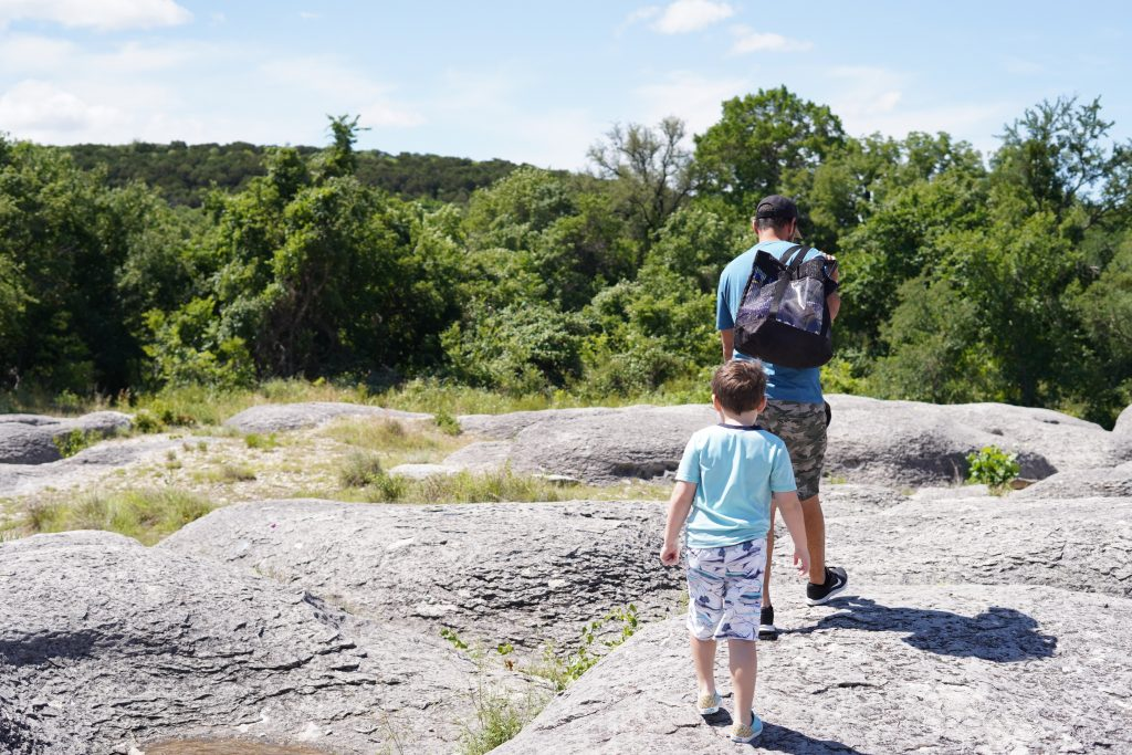 Man and little boy walking on the Big Rocks.   A Guide to Granbury, Texas