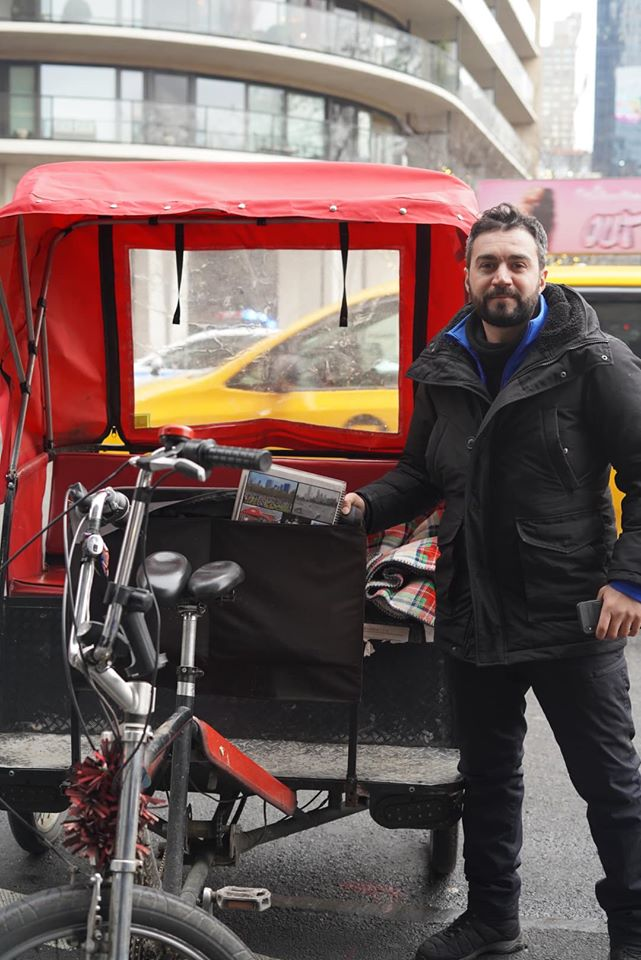 Man posing in front of Bike Carriage Ride.   New York City