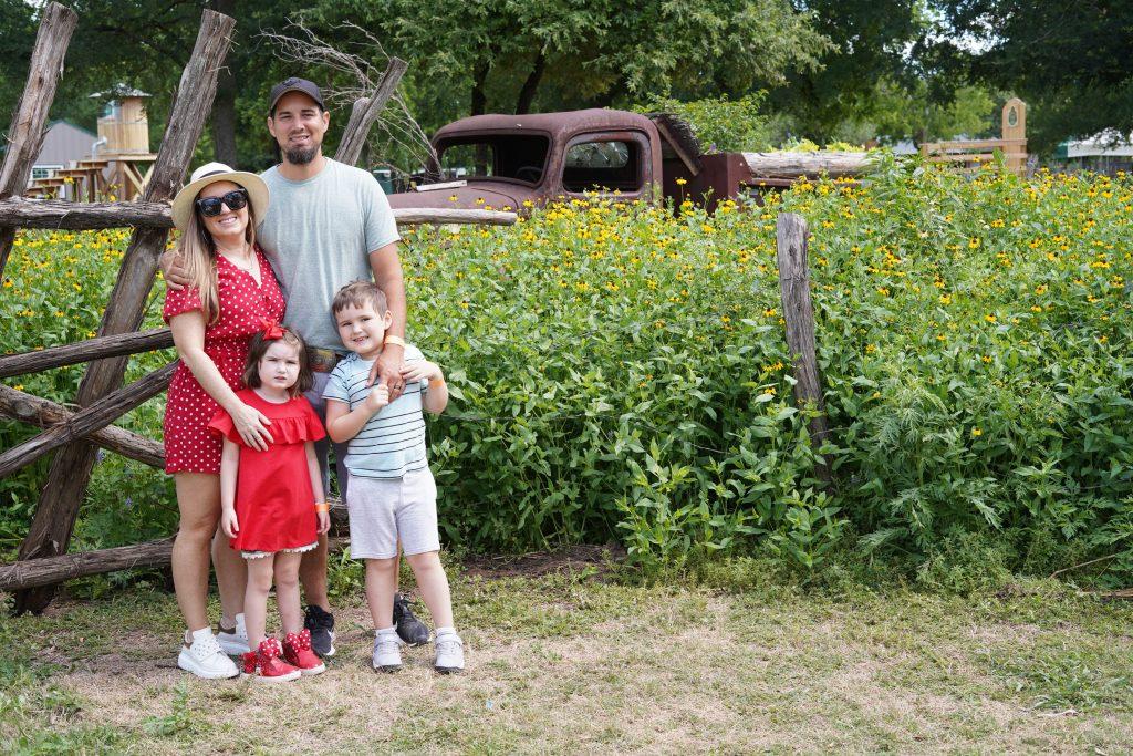 Family posing in front of the entrance of Blessington Fields. | Blessington Farms in Simonton, Texas