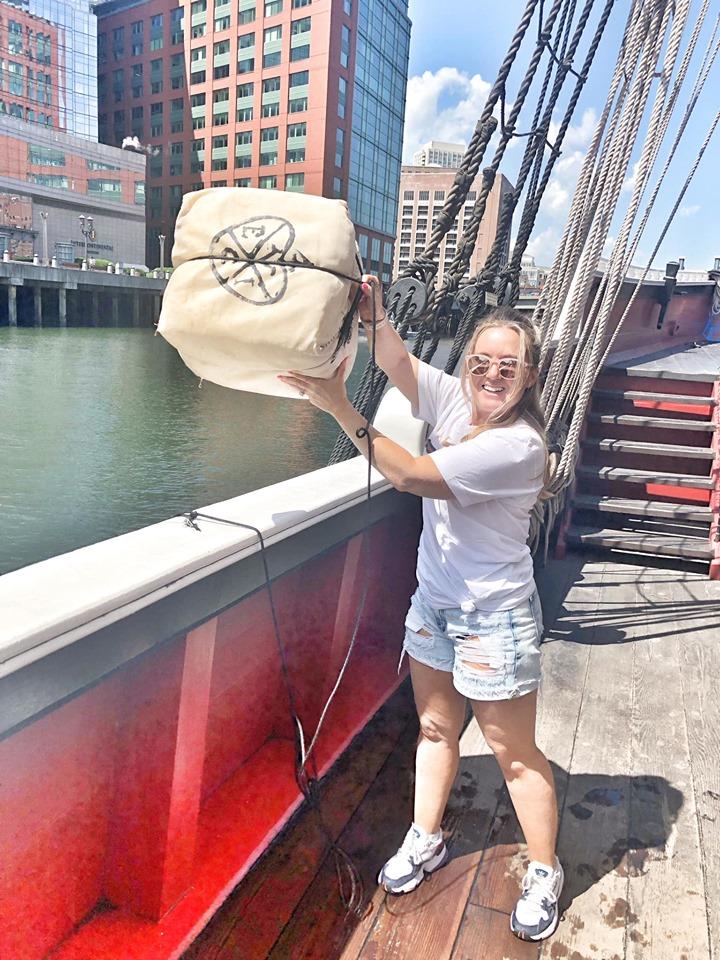 Woman on the Boston Tea Party ship pretending  to pour tea in Boston. | Boston, Massachusetts- Adult Getaway