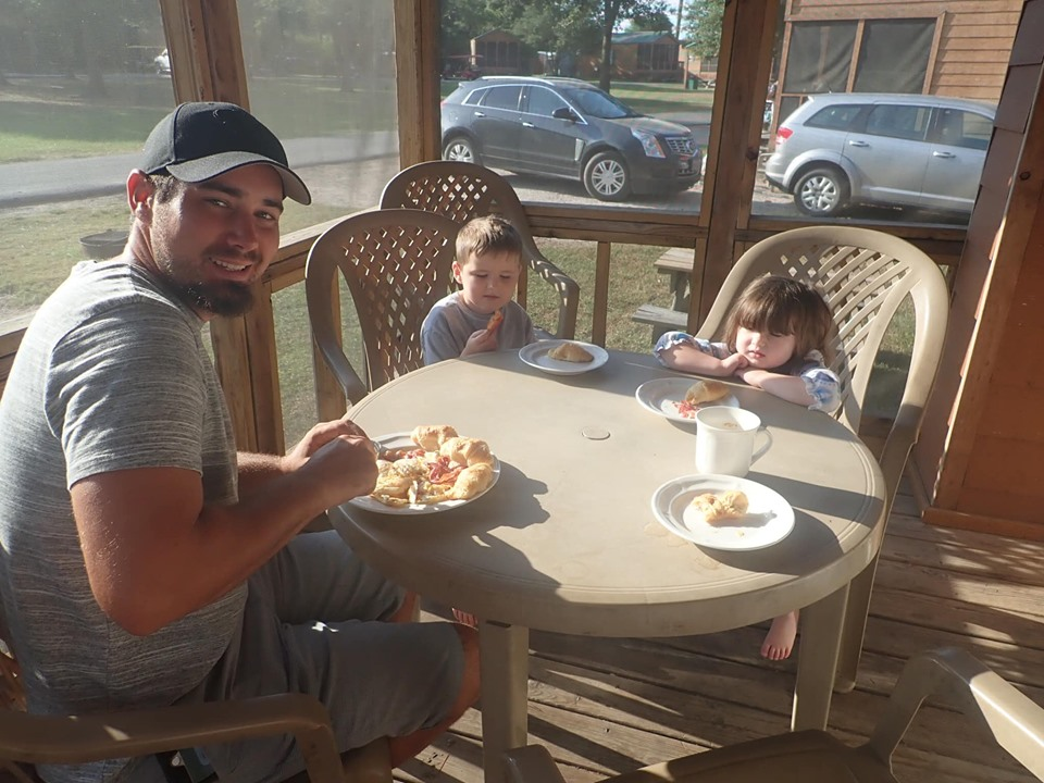 Family eating breakfast on porch of cabins at Jellystone in Texas.   Jellystone Park in Waller, Texas