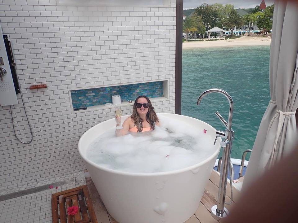 Woman taking a bubble bath in the over-water Bungalow in Jamaica.   Jamaica Over-Water-Bungalows