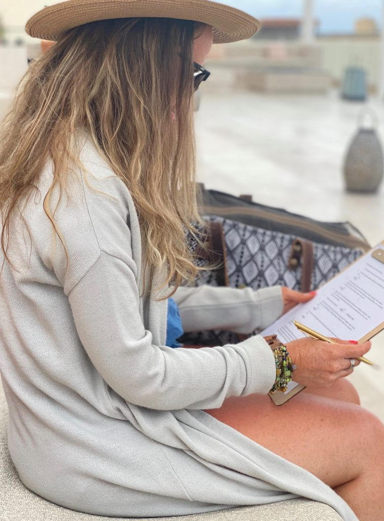 Woman sitting on a bench filling out paperwork with a clipboard. | A Guide to Nobu Hotel Los Cabos - A Relaxing Girls Trip