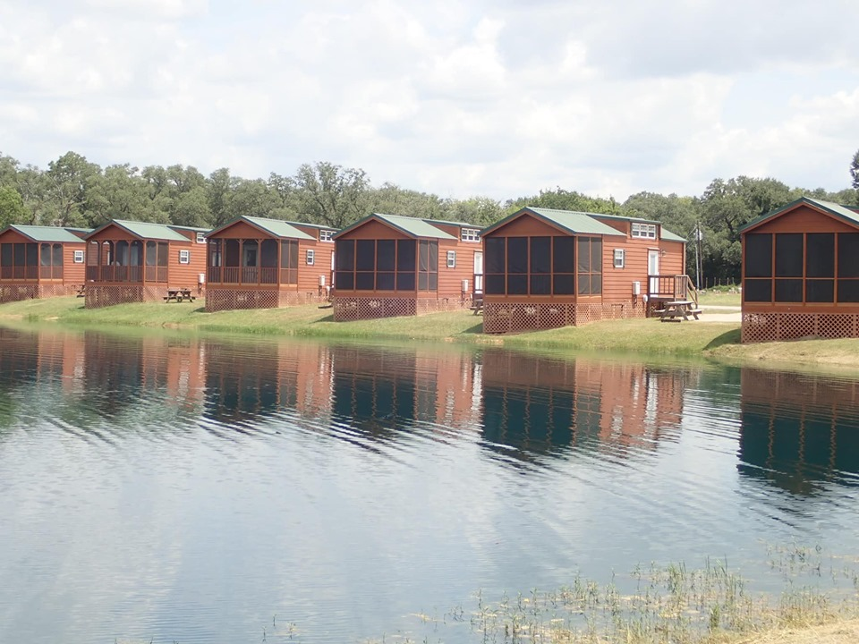 View of cabins by the lake at Jellystone in Texas.   Jellystone Park in Waller, Texas