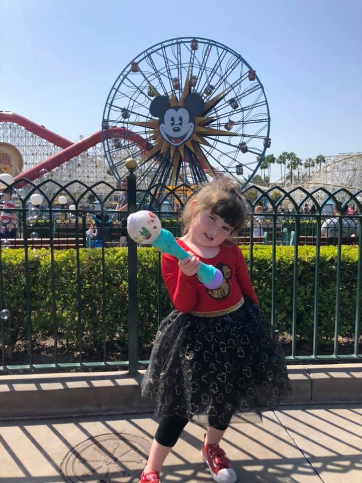 Little girl posing in front of Ferris Wheel in California Adventures in Disneyland.   Disneyland Resort Hotels, Anaheim; What you need to know.