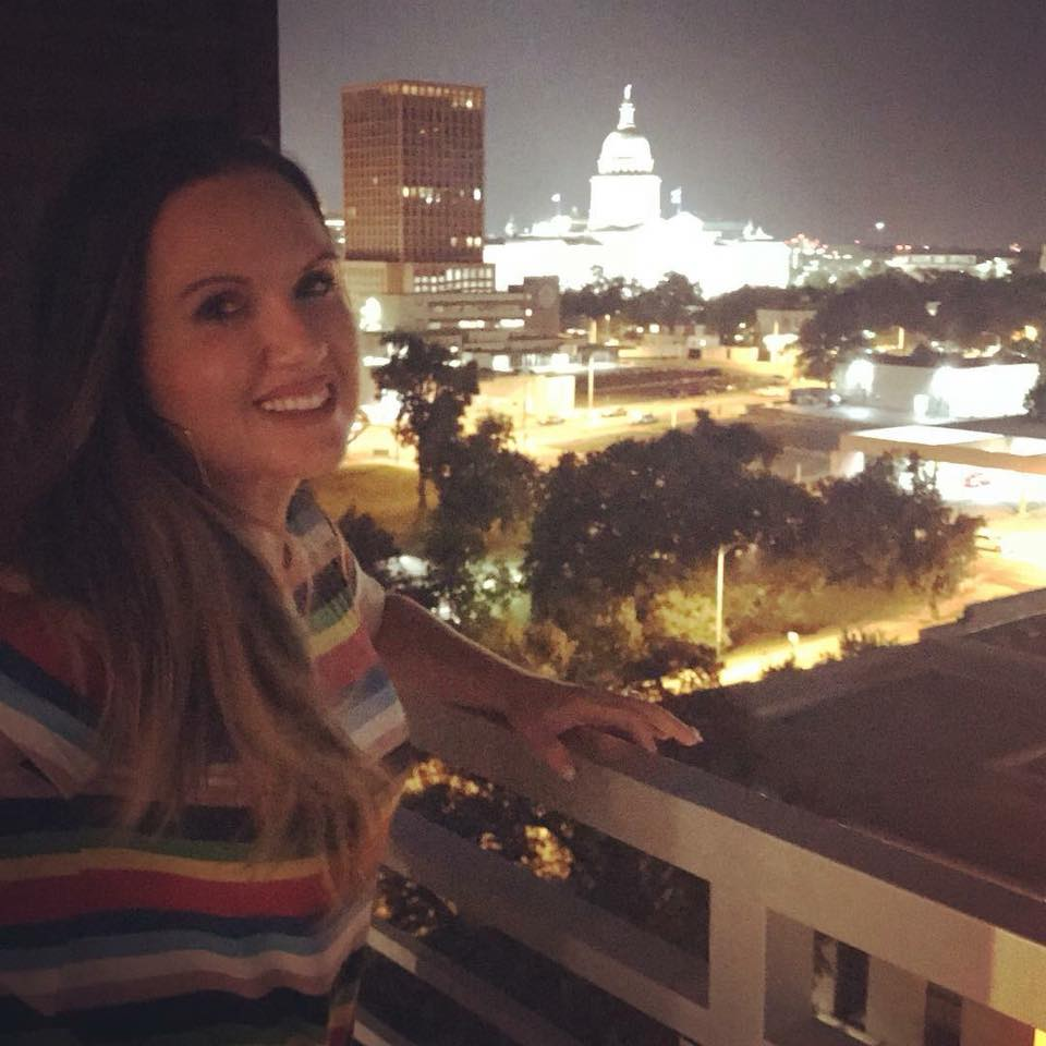 Woman posing with the state capitol in the background at night in Austin.  Weekend Guide to Austin, Texas