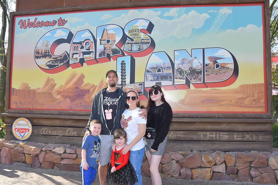 Family posing in front of the Welcome to Carsland sign at California Adventures in Disneyland.   Disneyland Resort Hotels, Anaheim; What you need to know.
