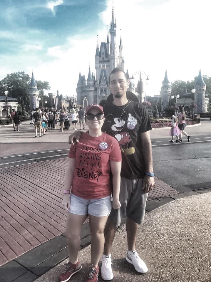 Couple posing in front of Magic Kingdom castle at Disney World.   Celebrating A Wedding Anniversary at Walt Disney World