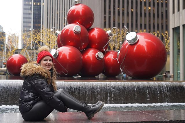 Woman posing on ledge of water feature with giant red Christmas ornaments in the background.   New York City