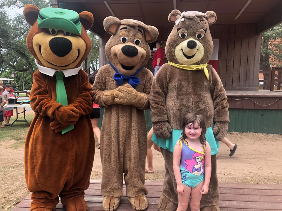 Little girl posing with three bear characters at Jellystone in Texas.   Jellystone Park in Waller, Texas