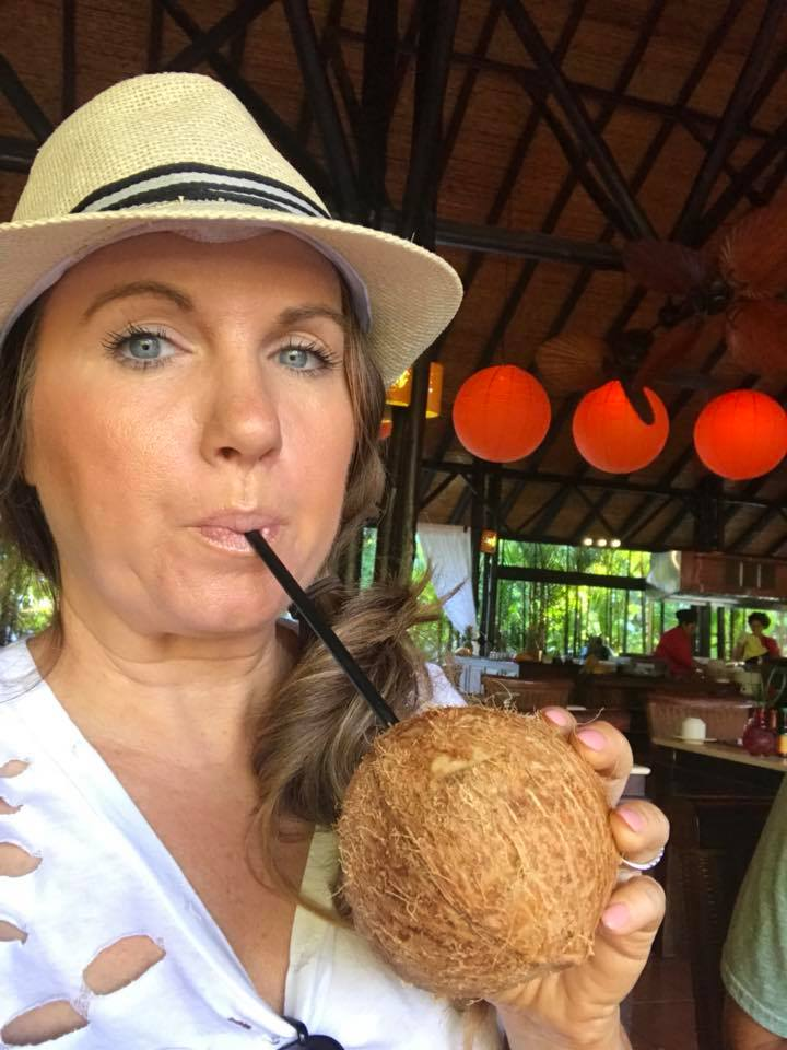 Woman taking a selfie drinking straight from a coconut at Nayara Spa and Gardens in La Fortuna.   Costa Rica, Arenal Volcano
