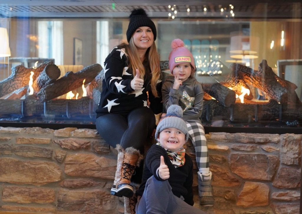 Woman with two kids smiling in a ski lodge. lobby.| Best Places to Visit in Colorado