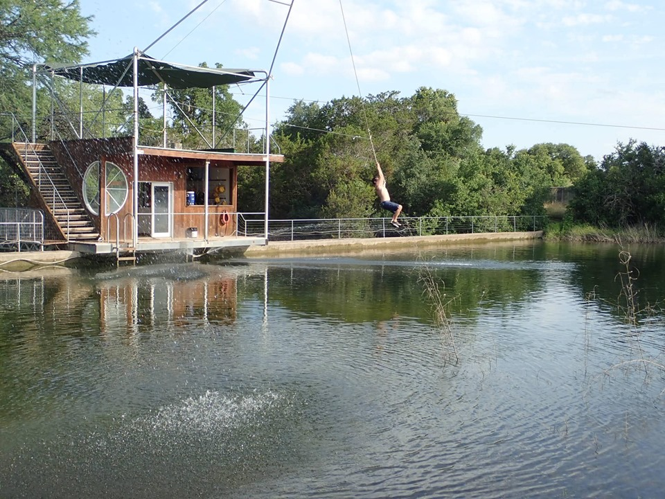 Man riding a zip line over the water at Cypress Valley. | Cypress Valley Canopy Tour in Austin, Texas