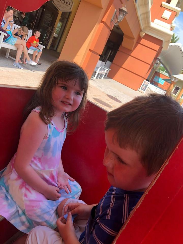 Two little kids riding a small train ride on the Destin Harbor Boardwalk in Destin.   Destin, Florida with the Kids