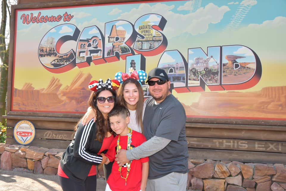 Family posing in front of Welcome to Carsland sign at Disneyland.   Disneyland Resort Hotels, Anaheim; What you need to know.