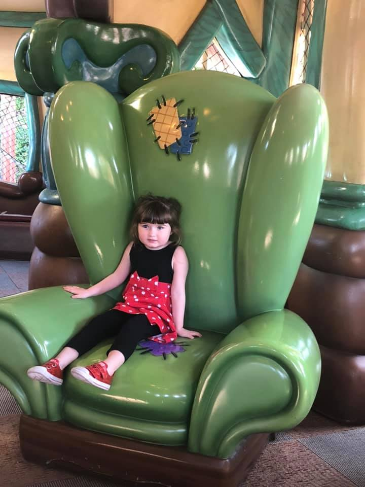 Little girl sitting on giant green chair in Goofy's Fun House at Disneyland.   Disneyland Resort Hotels, Anaheim; What you need to know.