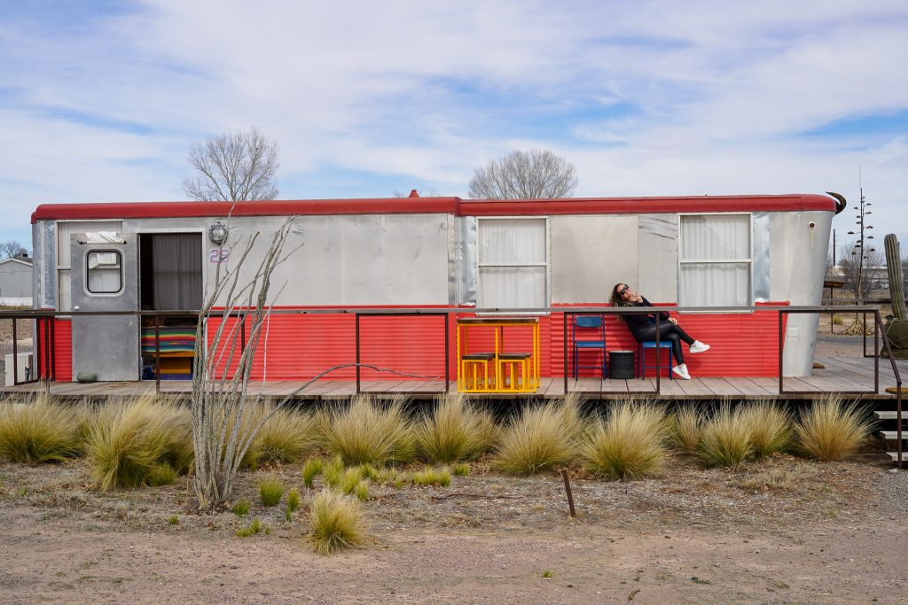 View of El Cosmico Trailer with woman sitting on patio. | Marfa, Texas- Where to Stay, What to do, & What to Eat