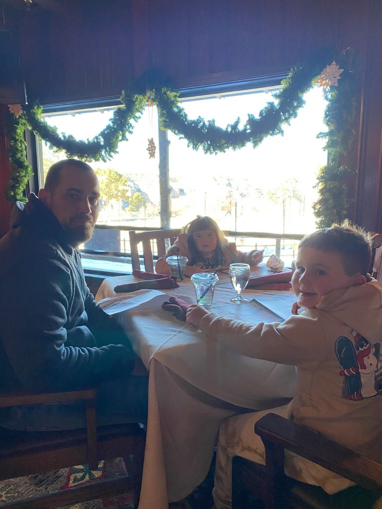 Family sitting at a table in a restaurant eating. | Visiting Grand Canyon in the Winter?