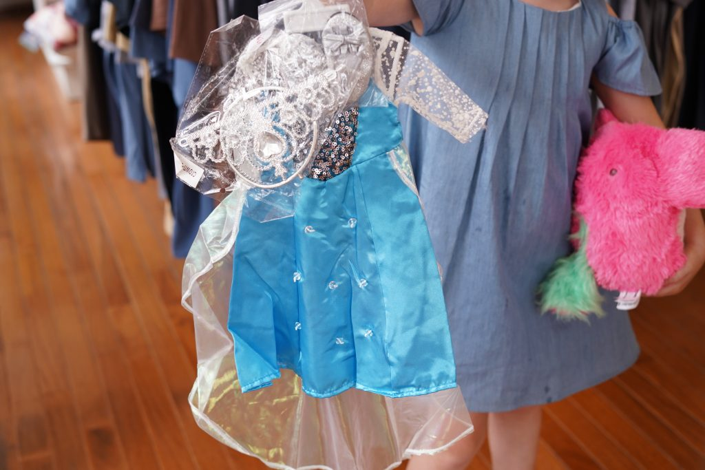 Little girl holding dress up clothes in Pickadillys American Girl Dolls store.   A Guide to Granbury, Texas