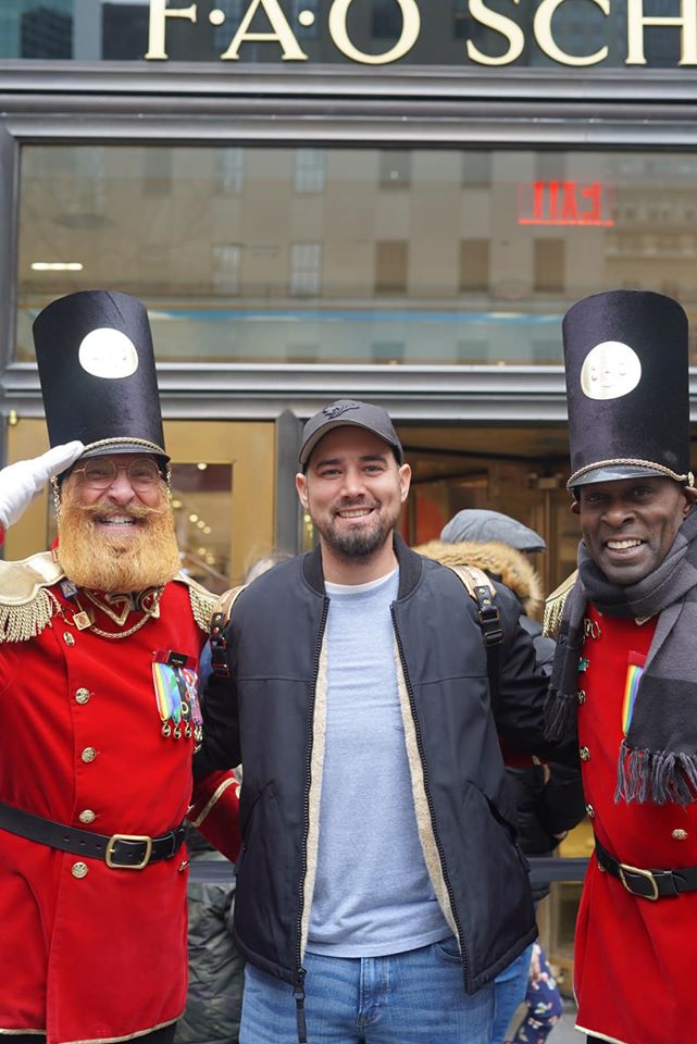 Man posing with toy soldier characters in front of FAO Schwartz Toy Store on the street.   New York City