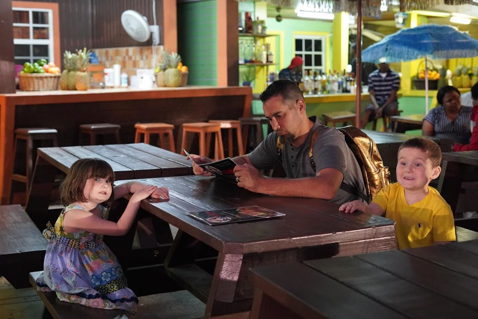 Family eating dinner at Fish Fry in Downtown Nassau.   Atlantis, Bahamas