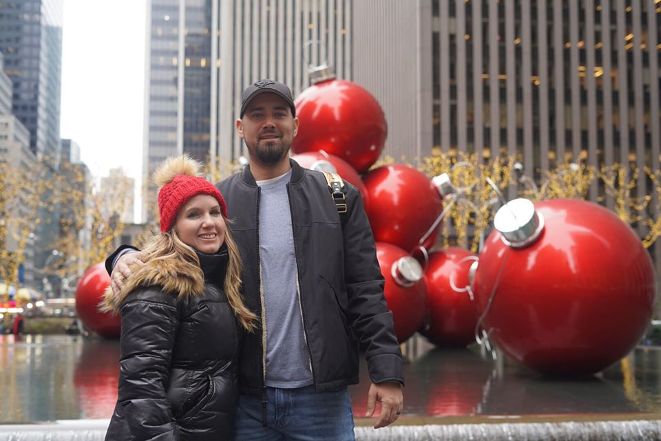 Couple posing in front of giant Christmas ornaments on the street.   New York City