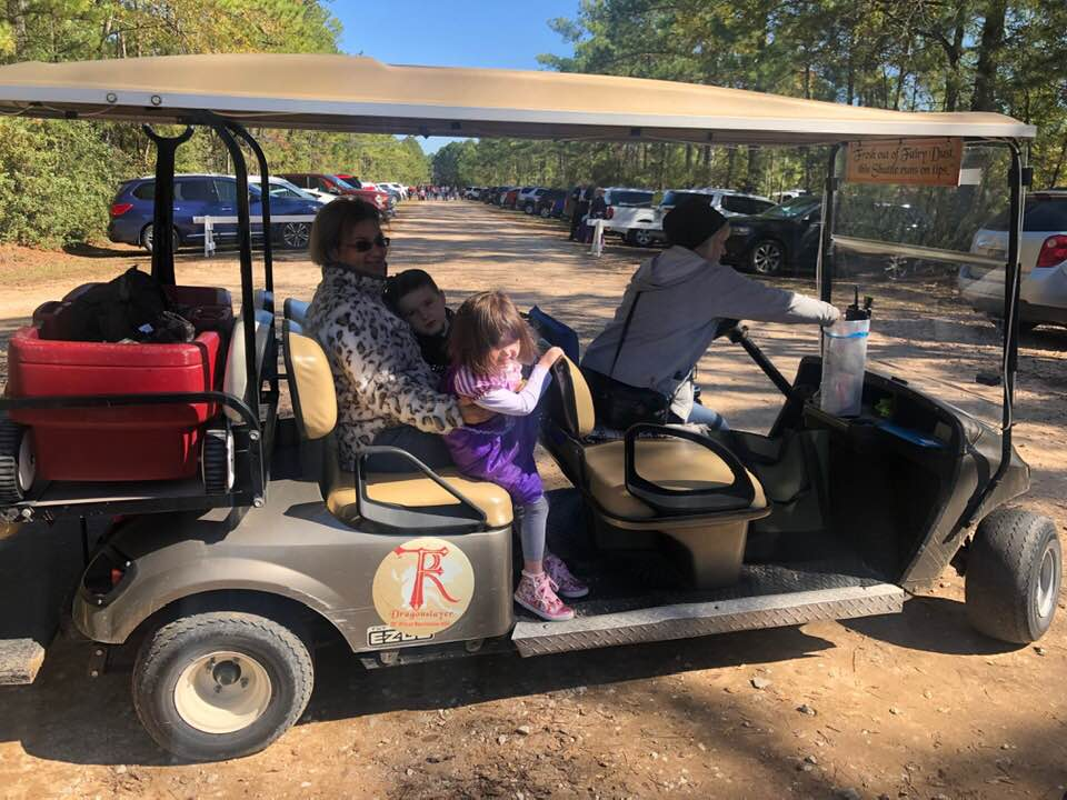 People riding a golf cart from the parking lot at the festival. | Texas Renaissance Festival